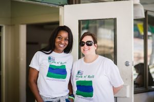 A young African American woman and a young white woman stand together smiling, both wearing white t-shirts with blue and green printing