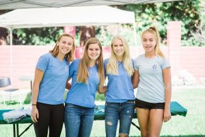 Four white teenager girls wearing blue t-shirts stand next to each other and look at the camera smiling.