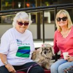Two older white women, one with white hair and a white t-shirt with blue and green printing, the other with blonde hair and a deep rose shirt. Both wear sunglasses and there is a small grey dog between them.