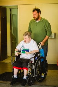 A white man in a white t-shirt with blue and green printing sits in a wheelchair. Behind him stands a white man with a brown beard wearing a green long sleeved shirt.
