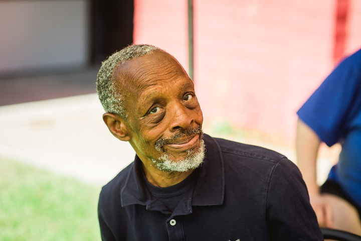 An older African American man with short grey hair and a short grey beard looks at the camera.