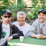 Three white men sit at a table. The man on the left wears a dark baseball cap and sunglasses and has a large birthmark on his face. The man in the center is middle aged with short grey hair. The man on the right is early middle aged and wears a Giants sweatshirt and a ball cap.