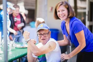 An older white man with glasses and a baseball cap show off his Wonder Woman temporary tattoo on his bicep. Behind him stands a smiling middle aged white woman with shoulder length brown hair and a blue shirt.