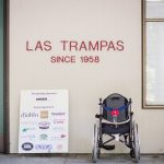 "A sign on a wall reads ""Las Trampas since 1958."" Below it is a sign with many corporate logos and a wheel chair."