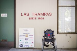 """A sign on a wall reads """"Las Trampas since 1958."""" Below it is a sign with many corporate logos and a wheel chair."""