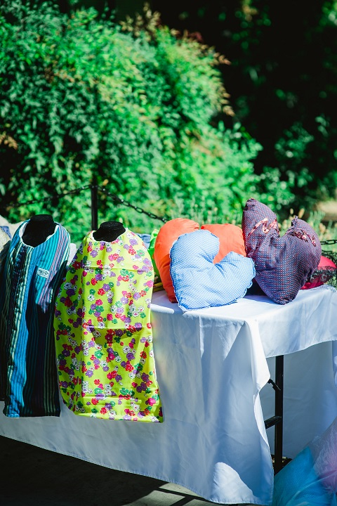 A display of pillows and bibs in colorful fabrics