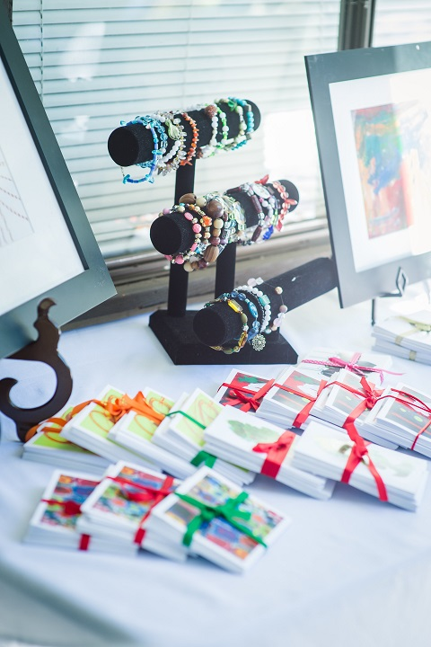 A display of packs of colorful notecards tied with ribbon and a rack of beaded bracelets on a table with a white cloth