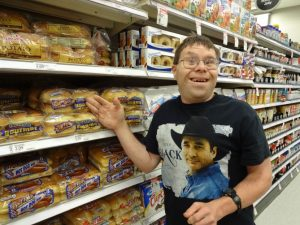Smiling man with glasses gestures toward a supermarket shelf.