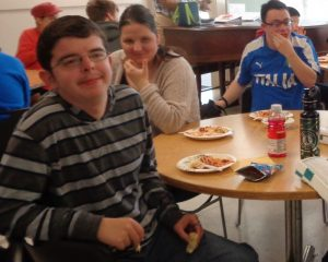 A young man with a striped shirt and glasses, a young woman with long brown hair, and a young man with a blue and white shirt and glasses sit at a table enjoying their food.