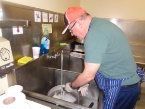 An older man in a red cap and green shirt washes dishes in a sink