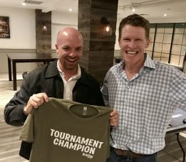 "Two smiling white men hold a tee shirt that reads ""Tournament Champion"""