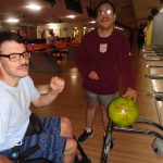 A man sits in a wheelchair. Another man holds a bowling ball. They are in a bowling alley.