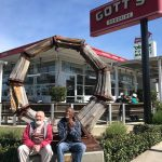 An older White man and an older African American man sit in front of the Gott's sign in Napa
