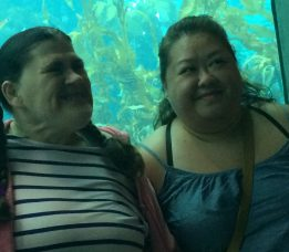 Two smiling women stand in front of an aquarium tank.